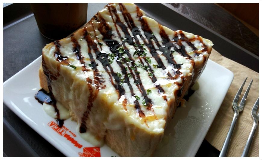 치즈가 녹여나온 빵에 초코시럽이 올려져 있는 모습